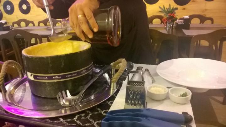Flambagem do queijo acontece na mesa como parte da apresentação do prato.